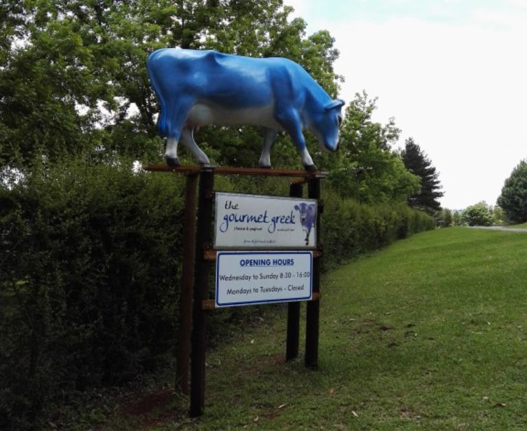 The Gourmet Greek Signboard with a blue cow